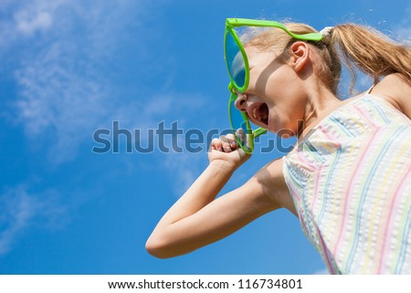 girl in big sunglasses looking at the sky