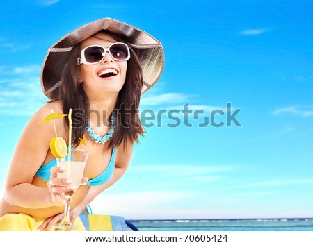 Girl in bikini drink juice through a straw.