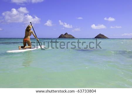 girl in bikini on a  stand uppaddle board in hawaii