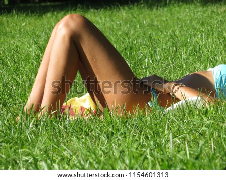 Girl in bikini sunbathing in a summer meadow. Female slender legs on the background of green grass, enjoying the sun, relaxation concept