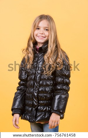 Girl in black coat on orange background. Child model smile with long blond hair. Kid beauty, look, hairstyle. Fashion, autumn style, trend. Happy childhood concept.