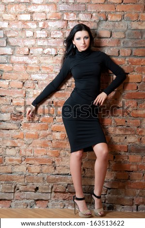 Girl in black dress. Brick wall #163513622