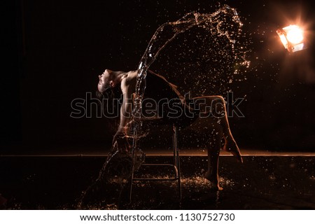 Stock Photo Girl in black dress on chair in water in a small pool, drops of water and dark background during a photoshoot with water