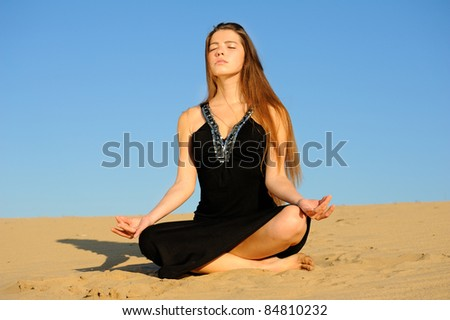 Girl in black dress sitting in a lotus position on the sand