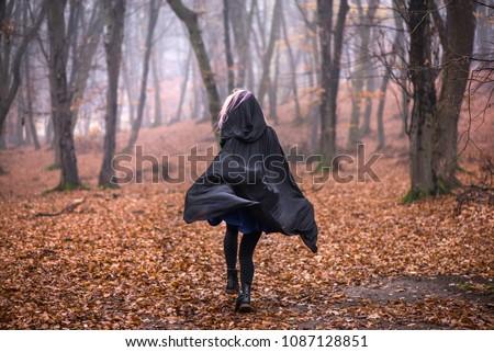 Girl in black hood running away from danger deep in dark forest. Thick fog all around. Scary autumn scene