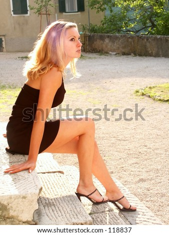 Girl in black miniskirt and naked legs sitting on the stairs