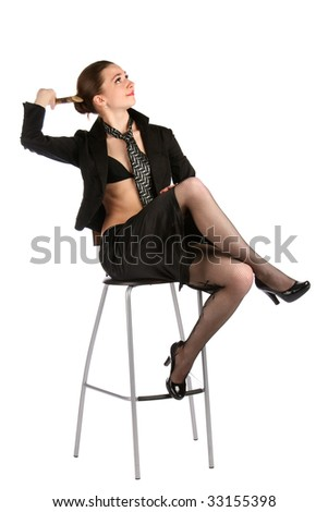 Girl in black suit with pencil sit on stool thinking. Isolated on white.