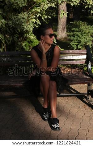 Girl in black walking in the park #1221624421