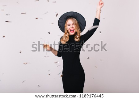 Stock Photo Girl in black witch attire gone wild during photoshoot with glitter confetti. Indoor portrait of laughing woman having fun at halloween masquerade and drinking champagne.