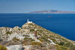 Girl in blue dress and hat posing on hill near Knidos Lighthouse, Datca province of Mugla, Turkey. At background Aegean Sea and Greek Kos Island are visible.