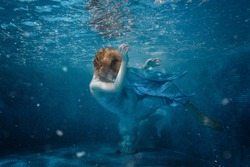 Girl in blue dress under water in the pool.
