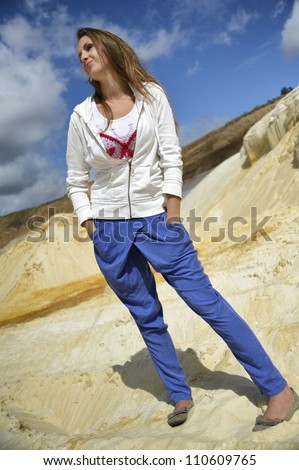 girl in blue pants and a white jacket on the bright sand