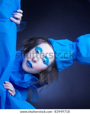 Girl in blue. Young woman in artistic image with bright visage and in blue hat.