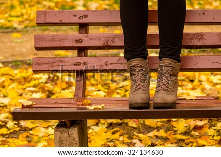 Girl in boots standing on a red bench with yellow birch leaves in the background. Autumn picture in a park. Cute fall image.