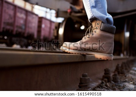 Girl in boots walks through the railroad tracks in autumn