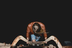 Girl in broth leather jacket climbing down fire escape ladder at night