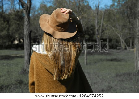Girl in brown hat and kint standing in beautiful green park on sunny day. Back view, copy space. Country style. Stock fotó ©