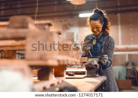 Girl in carpentry workshop doing wood job with protective glasses on. #1274017171