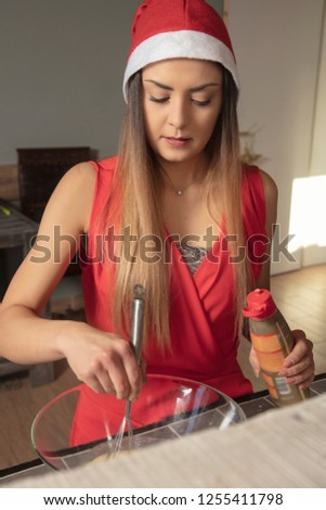 girl in Christmas clothing, is preparing to make a cake