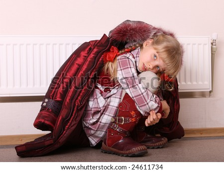 Girl in coat warm  near radiator.  Energy crisis.