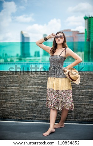 Girl in colorful cloth and sunglasses on the rooftop by the swimming pool with city background