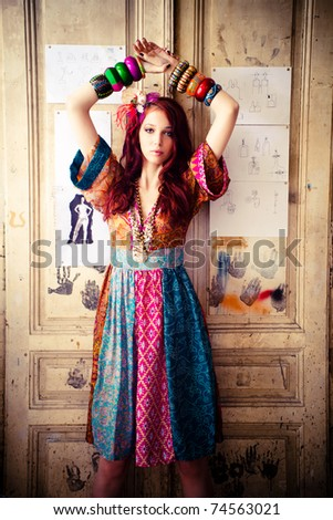 girl in colourful summer dress and lot of bracelets stand in front door