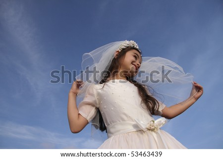 Girl in Communion dress against blue sky