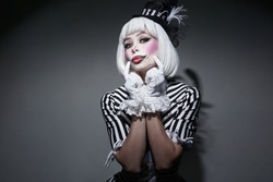 Girl in costume for Halloween holding.Sexy female in dress on gray background. Happy Halloween on the World. Holiday clown.