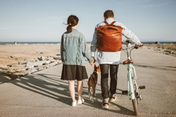 Girl in denim dress and jacket with man in jeans and blue shirt with leather brown backpack. Couple walks to sea on beach with basenji dog and holds hands, guy leads mint bike. Overall view from back.