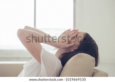 Girl in despair covers her face with hands sitting on a white sofa. Stressed woman at home headache pain female portrait. Preaty sad girl close face and head by hands sitting alone