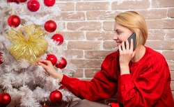 Girl in dress sit near christmas tree with ornaments. Woman cheerful hold smartphone enjoy mobile phone conversation. Waiting for christmas. Christmas or holiday phone message voicemail greeting.
