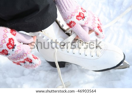 Girl in dress skates mittens tying shoelaces and prepare for skating