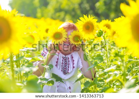 girl in embroidery hid eyes behind sunflowers. Happy woman among yellow flowers. Ukraine's Independence Day. National clothes of Ukraine.