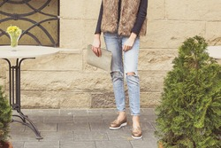 Girl in fake fur vest, jeans and a black sweater. Street style, urban fashion. Young woman in torn jeans and with stylish golden handbag in hand on the city streets.