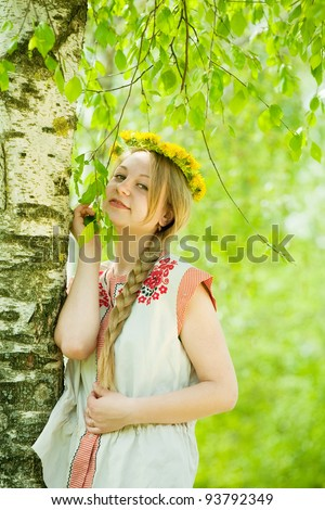 girl in flowers wreath and traditional clothes near birch