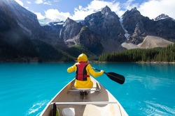 girl in front of a canoe in the mountains wearing a yellow jacket