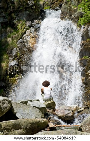 Girl in front of a waterfall.