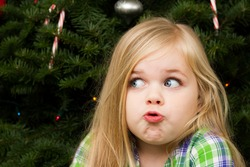 Girl in front of the christmas tree making a funny face