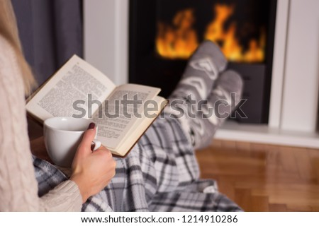 Girl in front of the fireplace reading book and warming feet on fire and legs are covered with blanket, in hand holds cup of hot tea. Winter and cold weather concept at home. Close up, selective focus