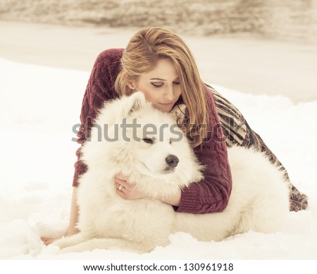 Girl in fur hat with samoyed dog in winter park