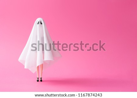 Girl in ghost costume against pastel pink background. Halloween party minimal concept.