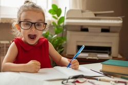 Girl in glasses for sight. A happy little girl opened her mouth with joy while learning lessons. Left-handed. International left-handed day.