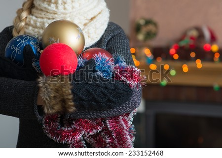 Girl in gloves holds a Christmas decoration