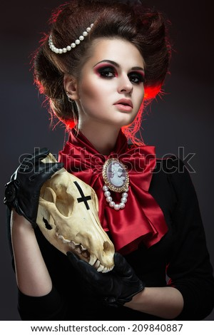 Girl in gothic art style with creative makeup and skull