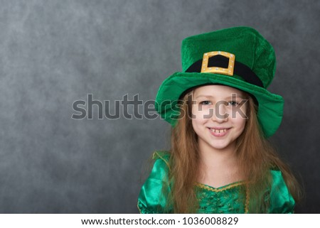 Girl in green emerald costume and leprechaun top hat with golden buckle