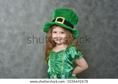 Girl in green emerald costume and leprechaun top hat with golden buckle