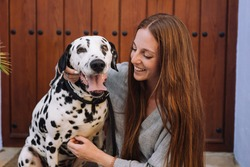 girl in grey dress with red hair smiling and hugging her Dalmatian dog