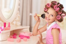 girl   in hair curlers  doing make up