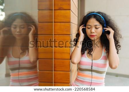 Girl in headphones enjoying her favorite song #220568584