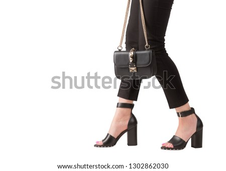 Girl in high-heeled shoes with a bag on a white background. Girl in trousers walks in high-heeled shoes. #1302862030